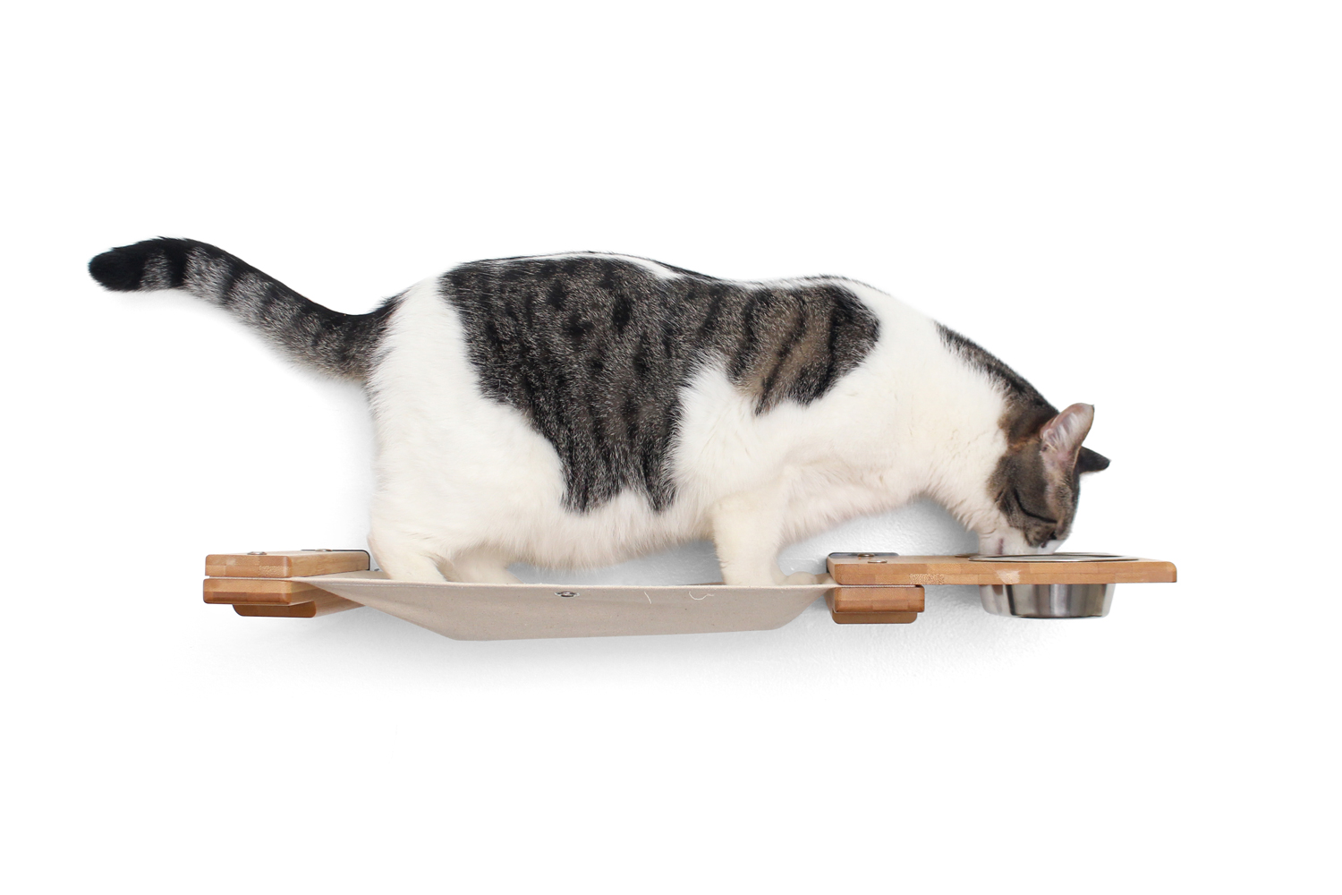 This photo displays a cat eating from the Feeder on the Feeder Lounge. This image shows the Feeder Lounge in Natural, a light brown stain, with Natural fabric, a light tan color.