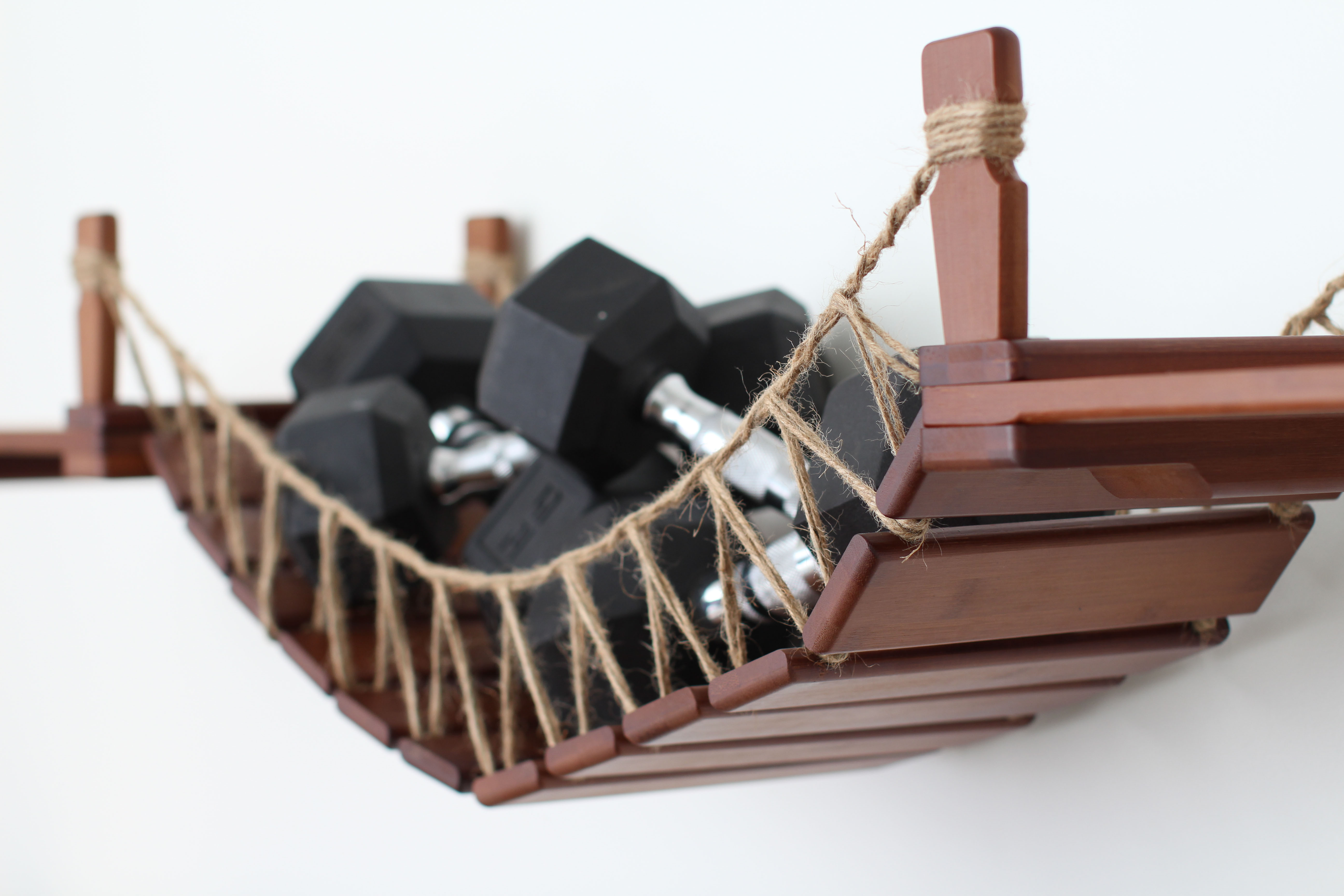 This photo displays the Bridge with Landings in English Chestnut, a dark brown stain, being weight tested with several hand weights.