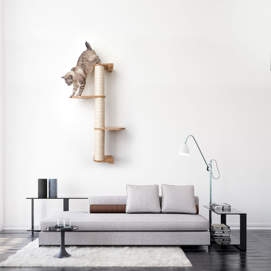 This image displays our cat playing on a three tier Deluxe Sisal Climbing Pole mounted in a living space. The Sisal Pole and Leaf Connectors are in Natural, a light brown stain.