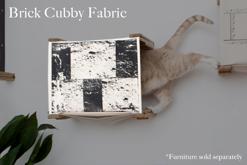 Cat cubby with black and white brick design, a tan cat is stepping from one shelf into the cubby.
