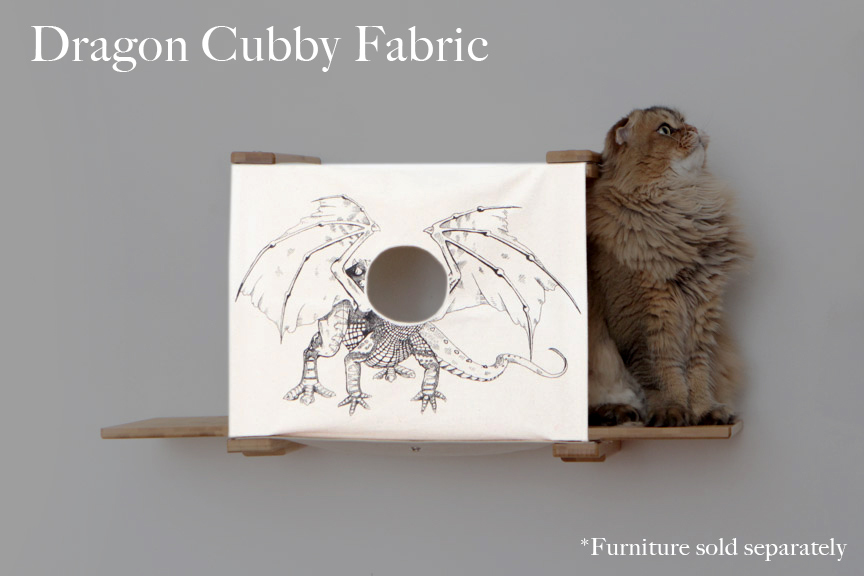 Cat cubby with baby dragon design, a fluffy tan cat is sitting on the right ledge. Where the baby dragons face would be is a small hole for a kitten to poke its head through.