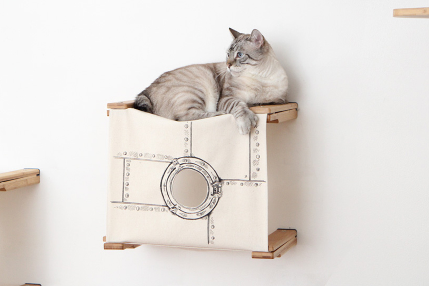 Wall mounted cat tunnel cubby with gray cat resting on top