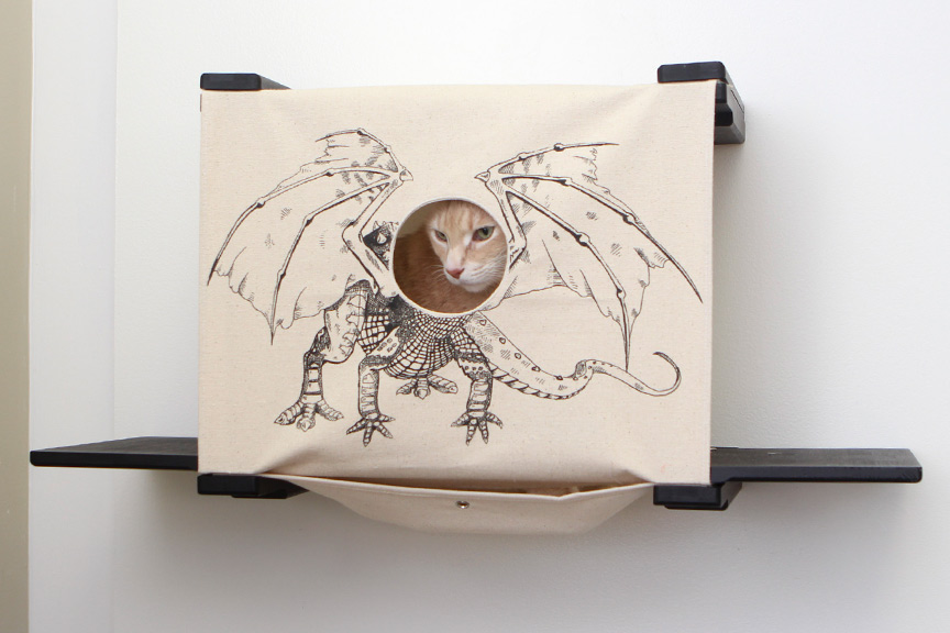 Wall mounted cat tunnel cubby with ledges. orange kitten poking head through hole in fabric